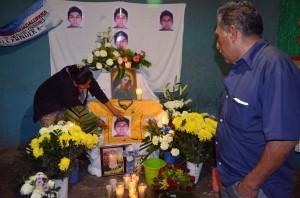 Ezequiel Mora, derecha, padre de Alexander Mora, uno de 43 estudiantes mexicanos desaparecidos desde septiembre observa mientras una persona no identificada toca una foto de su hijo en un altar en el pueblo de El Pericón. Foto: AP