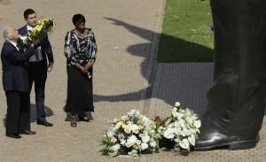 George Bizos (izquierda), abogado de derechos humanos que trabajó para el fallecido ex presidente de Sudáfrica Nelson Mandela, hace una ofrenda floral ante una estatua de bronce de nueve metros con la imagen del mandatario en el primer aniversario de su muerte. Foto: AP