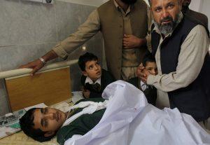 Un paquistaní consuela a un estudiante de pie junto a la cama de un niño herido en un atentado talibán sobre una escuela, en un hospital de Peshawar, Paquistán. Foto: AP