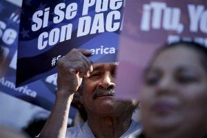 Un hombre aparece entre carteles durante una manifestación en apoyo del plan del presidente Barack Obama para proteger de la deportación a más de cuatro millones de personas que viven en Estados Unidos sin permiso. Foto: AP