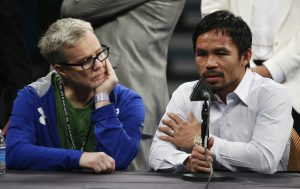 """FILE - In this May 2, 2015 photo, trainer Freddie Roach, left, listens as Manny Pacquiao answers questions during a press conference following his welterweight title fight against Floyd Mayweather Jr. in Las Vegas. Pacquiao could face disciplinary action from Nevada boxing officials for failing to disclose a shoulder injury before the fight. Nevada Athletic Commission Chairman Francisco Aguilar said that the state attorney general's office will look at why Pacquiao checked """"no"""" a day before the fight on a commission questionnaire asking if he had a shoulder injury. (AP Photo/John Locher)"""