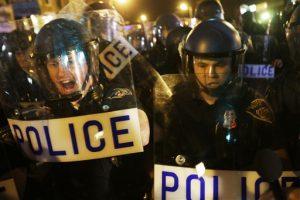 Policía en material antimotines repele a los medios y a una multitud reunida tras la entrada en vigor del toque de queda a las 10 de la noche, el jueves 30 de abril de 2015 en Baltimore. El toque de queda se impuso tras los disturbios desencadenados por la muerte de Freddie Gray bajo custodia policial. (AP Foto/David Goldman)