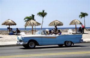 """Un grupo de personas disfruta de una playa artificial mientras un auto pasa por el malecón el jueves 21 de mayo de  2015 en La Habana, Cuba. La playa fue creada como parte de la muestra """"Detrás del Muro"""" de la Bienal de Arte de La Habana. (Foto AP/Desmond Boylan)"""