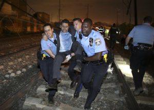 Personal de emergencia ayuda a un pasajero en el lugar de un accidente de tren, el martes 12 de mayo de 2015 en Filadelfia. Un tren de Amtrak con destino a Nueva York descarriló y se estrelló en Filadelfia.  (AP Foto/Joseph Kaczmarek)