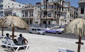 """Un grupo de personas disfruta de una playa artificial mientras un auto convertible clásico lleva a unos novios por el malecón de La Habana, el jueves 21 de mayo de 2015 en La Habana, Cuba. La playa fue creada como parte de la muestra """"Detrás del Muro"""" de la Bienal de Arte de La Habana.  (Foto AP/Desmond Boylan)"""