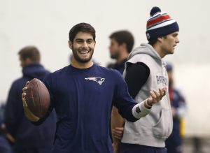 New England Patriots backup quarterback Jimmy Garoppolo, left, smiles while holding a football as Patriots starting quarterback Tom Brady stands by during a football team walkthrough in Foxborough, Mass., Friday, Jan. 23, 2015. (AP Photo/Elise Amendola)