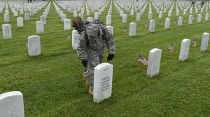 "Third U.S. Infantry Regiment (The Old Guard) Pfc. Kaitlyn Bolde of Scotia, N.Y., places a flag in front of a headstone at Arlington National Cemetery in Arlington, Va., Thursday, May 21, 2015.""Flags In"" is an annual tradition that is reserved for The Old Guard since its designation as the Army's official ceremonial unit in 1948. They conduct the mission annually at Arlington National Cemetery and the U.S. Soldiers' and Airmen's Home National Cemetery prior to Memorial Day to honor the nation's fallen military heroes. (AP Photo/Susan Walsh)"