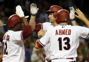 Arizona Diamondbacks Mark Trumbo greets teammates Nick Ahmed (13) and Rubby De La Rosa (12) at home plate after Trumbo hit a three run home run against the Washington Nationals during the fourth inning of a baseball game, Tuesday, May 12, 2015, in Phoenix. (AP Photo/Matt York)