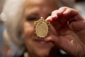 La asistente de galería Sandra Handley posa para fotógrafos con un mechón de pelo de Wolfgang Amadeus Mozart, contenido en un relicario dorado del siglo XIX, el martes 26 de mayo del 2015 en la casa de subastas Sotheby's en Londres. El mechón podría facturar hasta 12.000 libras esterlinas (más de $18.000 dólares) el jueves en la venta de música, libros y manuscritos continentales y rusos de la rematadora. (AP Foto/Matt Dunham)