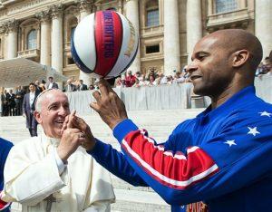 El papa Francisco sonríe mientras el jugador de los Harlem Globetrotters, Flight Time Lang, le enseña cómo sostener el balón con un dedo. Foto: AP