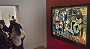 """El óleo de Pablo Picasso """"Las mujeres de Arhel (Versión O)"""" es exhibido el 1 de mayo de 2015 en un tipo de galería antes de que la sacara a la venta la casa de subastas Christie's, en Nueva York. El cuadro se vendió en 179 millones de dólares, una cantidad sin precedentes para una obra de arte vendida en subasta, el lunes 11 de mayo de 2015. Al fondo a la derecha es mostrada una escultura de bronce de tamaño natural """"Hombre señalando"""", del suizo Alberto Giacometti, que Christie's también podría a subasta. (AP Foto/Bebeto Matthews)"""