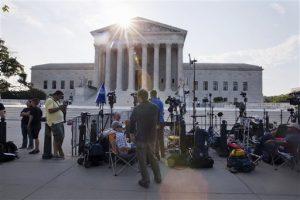 Periodistas hacen guardia frente a la Corte Suprema antes de que se diera a conocer el fallo sobre una controversia a la ley de seguros de salud. Foto: AP