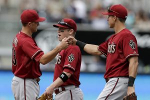 Arizona Diamondbacks' Nick Ahmed, left, celebrates with teammates Jake Lamb, right, and Aaron Hill, center, after defeating the San Diego Padres in a baseball game Sunday, June 28, 2015, in San Diego. The Diamondbacks won 6-4. (AP Photo/Gregory Bull)
