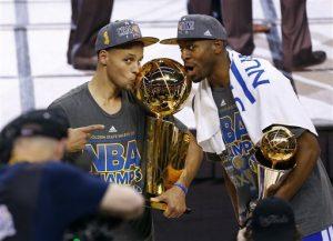 Stephen Curry, de los Warriors, besa el trofeo junto a su compañero Andre Iguodala, luego de que el equipo se coronó en la final de la NBA. Foto: AP