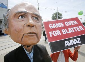 A protester wearing a mask depicting FIFA President Sepp Blatter stands in front of the building where the 65th FIFA congress takes place in Zurich, Switzerland, Friday, May 29, 2015. Protesters from the global campaign movement Avaaz demand the resignation of  Blatter over the FIFA corruption scandal and rights abuses of World Cup construction workers in Qatar. (AP Photo/Michael Probst