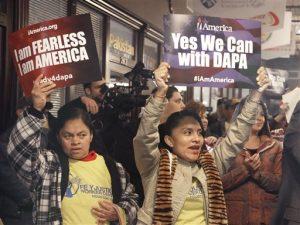 """Manifestantes en pro de los inmigrantes sostienen carteles durante un acto en Houston el martes 17 de febrero de 2015 en el que se les asesoraría para solicitar permisos de trabajo y evitar ser deportados de acuerdo con las acciones ejecutivas anunciadas por el presidente Barack Obama. El letrero de la izquierda afirma: """"Soy intrépido. Yo soy Estados Unidos"""", y el de la derecha dice: """"Sí podemos con el DAPA"""" (Programa de Acción Diferida para Padres). (Foto AP/Pat Sullivan)"""