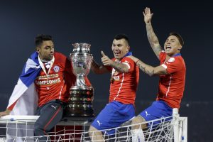 Chile's Gary Medel, center, and Chile's Eduardo Vargas, right, hold the trophy on top of the goal post after defeating Argentina in the Copa America final soccer match at the National Stadium in Santiago, Chile, Saturday, July 4, 2015. Chile became Copa America champions for the first time after defeating Argentina in a penalty shootout. (AP Photo/Ricardo Mazalan)