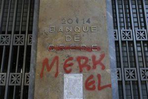 """Pintura roja cubre las palabras Banco de Grecia para que se lea """"Banco de Merkel"""" en referencia a la canciller alemana, en Atenas. Foto: AP"""