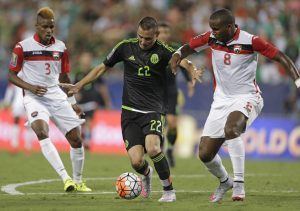 Mexico's Paul Aguilar (22) drives between Trinidad & Tobago's Khaleem Hyland (8)  and Joevin Jones (3) during the first half of a CONCACAF Gold Cup soccer match in Charlotte, N.C., Wednesday, July 15, 2015. (AP Photo/Gerry Broome)