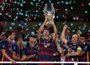 Barcelona's Sergio Busquets lifts the trophy after winning the UEFA Super Cup soccer match between FC Barcelona and Sevilla FC at the Boris Paichadze Dinamo Arena stadium, in Tbilisi, Georgia, on Wednesday, Aug. 12, 2015. Barcelona won 5-4. (AP Photo/Ivan Sekretarev)
