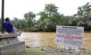 Un letrero advierte a las personas que no se metan al río Animas en lo que dura la coloración amarillenta y naranja del río a causa de un derrame de aguas residuales de una mina antigua en el parque Berg, en la localidad de Farmington, Nuevo México. Foto: AP