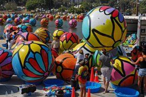 Varios voluntarios inflan eseferas para colocarlas en el lago del parque MacArthur de Los Ángeles, como parte de una instalación artística de Portraits of Hope. Foto: AP