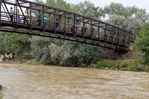 Varias personas observan el Río Animas desde un puente mientras aguas residuales de color mostaza mezcladas con metales pesados fluyen en la corriente en el Parque Berg en Farmington, Nuevo México. Foto: AP