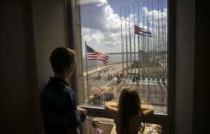 Dos niños contemplan desde la ventana de su casa las banderas de EU y Cuba a unos metros del malecón habanero. Foto: AP
