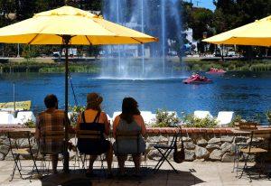 Visitantes del Echo Park Lake cerca del centro de Los Angeles se protegen del fuerte sol el viernes 14 de agosto de 2015. (Foto AP/Richard Vogel)