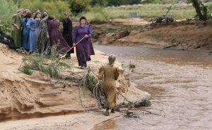 Miembros de la comunidad buscan a un lado de un riachuelo después de la inundación del pasado martes. Foto: AP