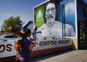 Un hombre, guitarra al hombro, pasa frente a una imagen del actor Danny Trejo pintada por el muralista Levi Ponce. Foto: AP