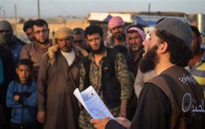 """En esta foto de archivo publicada el 14 de mayo de 2015 por un sitio extremista, la cual ha sido verificada y es consecuente con otro reporte de la AP, un miembro de la policía del grupo Estado Islámico conocido como """"Hisba"""" lee un veredicto dictado por un tribunal islámico en Siria. Foto: AP"""