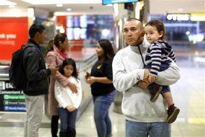 Gabriel Mejía sostiene a su hijo estadounidense Elías, de un año, mientras espera a otros dos hijos nacidos en El Salvador en el aeropuerto. Foto: AP