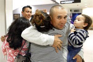 Gabriel Mejía abraza a su hija Wendy, de 16 años, mientras sostiene en un brazo a su hijo Elías, de un año, en el aeropuerto de Baltimore. Foto: AP