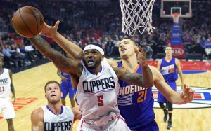Los Angeles Clippers forward Josh Smith, center, grabs a rebound away from Phoenix Suns center Alex Len, right, of Ukraine, as forward Blake Griffin, lower left, watches during the first half of an NBA basketball game, Monday, Nov. 2, 2015, in Los Angeles. (AP Photo/Mark J. Terrill)
