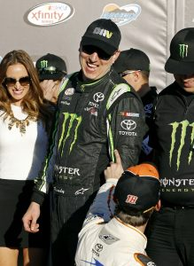 Kyle Busch, top, is congratulated in Victory Lane by fellow driver Daniel Suarez (18) after winning the NASCAR Xfinity Series auto race at Phoenix International Raceway, Saturday, Nov. 14, 2015, in Avondale, Ariz. (AP Photo/Ralph Freso)