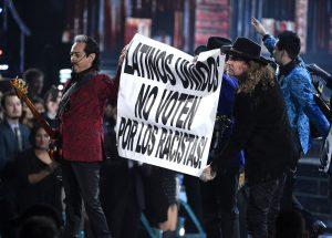 """Los Tigres del Norte y Maná sostienen un letrero que dice """"Latinos unidos no voten por los racistas"""" durante un número musical en la 16ª entrega de los Latin Grammy. Foto: AP"""