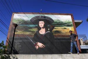 El muralista Levi Ponce posa frente a un mural que pintó en el barrio Pacoima de Los Angeles, en el que la Mona Lisa aparece con un sombrero de charro. Foto: AP