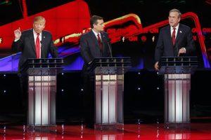 Donald Trump, a la izquierda, y Jeb Bush, a la derecha, hablan ante la mirada de Ted Cruz durante el debate republicano de CNN en el hotel y casino Venetian de Las Vegas. Foto: AP
