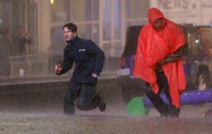 Varias personas corren bajo un aguacero en medio del sonido de sirenas que advierten sobre una tormenta en el centro de Dallas, Texas, el sábado 26 de diciembre. Foto: AP