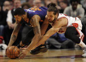 Chicago Bulls' Joakim Noah (13), battles Phoenix Suns' Markieff Morris (11), for a loose ball during the first half of a basketball game Monday, Dec. 7, 2015, in Chicago. (AP Photo/Paul Beaty)