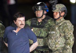 Joaquín Guzmán mira a la prensa mientras es escoltado por militares. Foto: AP