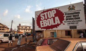 """Gente pasa frente a un letrero que dice """"STOP EBOLA"""" (Paren al ébola) que es parte de la campaña para liberar a Sierra Leona del ébola en la ciudad de Freetown. Foto: AP"""