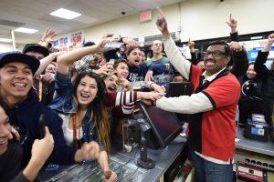 El dependiente de una tienda 7-Eleven M. Faroqui celebra con clientes la noticia sobre que la tienda vendió un boleto ganador en la lotería Powerball en Chino Hills, California. Foto: AP
