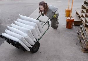Christine Bristor, de Barnes Supply Co. empuja una carretilla cargada con productos para derretir el hielo en Durham, North Carolina. Foto: AP