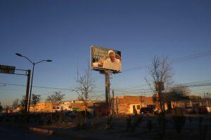 """El sol de la tarde ilumina un cartel gigantesco con una imagen del papa Francisco y una leyenda que dice """"Juárez es amor, estamos preparados"""". Foto: AP"""