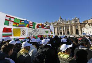 Fieles reunidos cerca de una pancarta adornada con las banderas de varios países y un mensaje escrito que dice: Gracias Papa Francisco, aguardan el inicio de la misa del Angelus en la Plaza de San Pedro. Foto: AP