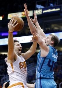 El bosnio Mirza Teletovic, de los Suns de Phoenix, dispara junto a Cody Zeller, de los Hornets de Charlotte, en el duelo realizado el miércoles. Foto: AP