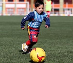Martaza Ahmadi, un niño afgano de cinco años seguidor del futbolista Lionel Messi, juega al fútbol en el estadio de la federación afgana de fútbol en Kabul, Afganistán, el martes 2 de febrero de 2016. (AP Foto/Rahmat Gul)