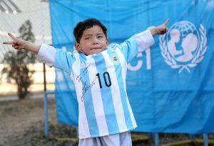 En esta foto suministrada por UNICEF, el niño afgano Murtaza Ahmadi posa con una camiseta de la selección de Argentina firmada por Lionel Messi el jueves, 25 de febrero de 2016, en Kabul, Afganistán.  (Mahdy Mehraeen/UNICEF via AP)